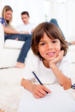 Smiling little boy drawing lying on floor Stock Photography