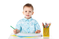 Smiling little boy draws with crayons Royalty Free Stock Photography