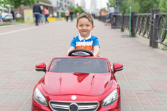 Smiling little boy driving by toy car. Active leisure and sports for kids. Portrait of happy little kid on the street. Funny cute. Children making vacations and Royalty Free Stock Photography