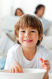 Smiling little boy eating chips lying on the floor Royalty Free Stock Images