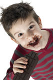 Smiling little boy eating chocolate Royalty Free Stock Image