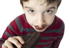 Smiling little boy eating chocolate Stock Images
