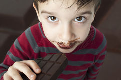 Smiling little boy eating chocolate Royalty Free Stock Photography