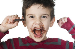 Smiling little boy eating chocolate Royalty Free Stock Photo