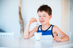 Smiling little boy eating delicious yogurt Royalty Free Stock Image
