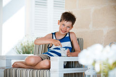 Smiling little boy eating delicious yogurt Stock Photo