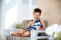 Smiling little boy eating delicious yogurt Royalty Free Stock Photography