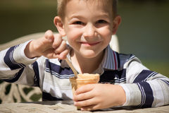 Smiling little boy eating ice-cream Stock Photos