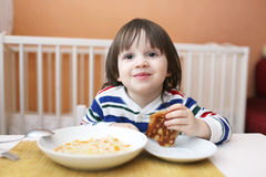 Smiling little boy eating soup Stock Images