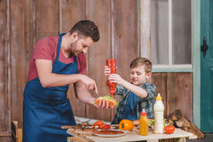 Smiling little boy with father cooking hot dog at backyard Stock Photography