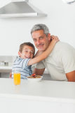 Smiling little boy giving hug to his father during breakfast. In kitchen Stock Photography
