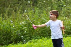 Smiling little boy in glasses plays with soap bubbles. In green forest Stock Images