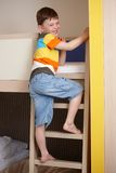 Smiling little boy going up the ladder of bunk bed Stock Image