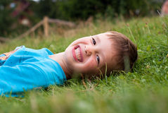 Smiling little boy in the grass stock photography