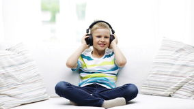 Smiling little boy in headphones at home Stock Image
