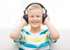 Smiling little boy with headphones at home Stock Photos