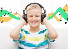 Smiling little boy with headphones at home Stock Photography