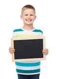 Smiling little boy holding blank black chalkboard Royalty Free Stock Images
