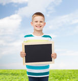 Smiling little boy holding blank black chalkboard Royalty Free Stock Images