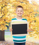 Smiling little boy holding blank black chalkboard Royalty Free Stock Photo