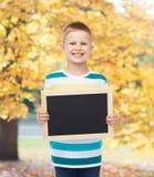 Smiling little boy holding blank black chalkboard Royalty Free Stock Photo