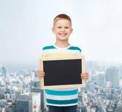 Smiling little boy holding blank black chalkboard Stock Image