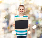 Smiling little boy holding blank black chalkboard Stock Image