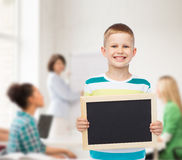 Smiling little boy holding blank black chalkboard Stock Photography