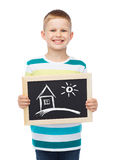 Smiling little boy holding chalkboard with home Royalty Free Stock Photos