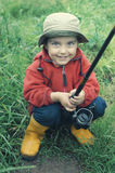 Smiling little boy holding fishing rod Royalty Free Stock Photos