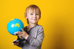 Smiling little boy holding globe in hands - isolated on yellow. Stock Photo