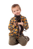 Smiling little boy holding his puppy Royalty Free Stock Photos