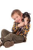 Smiling little boy holding his puppy Royalty Free Stock Images