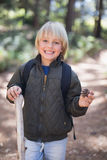 Smiling little boy holding pine cone while standing in forest Stock Images