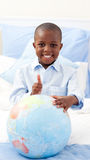 Smiling little boy holding a terrestrial globe Royalty Free Stock Photo