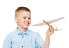 Smiling little boy holding a wooden airplane model Royalty Free Stock Photos