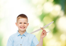 Smiling little boy holding a wooden airplane model Stock Photos