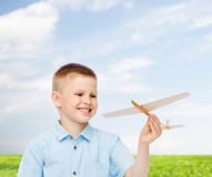 Smiling little boy holding a wooden airplane model Royalty Free Stock Images