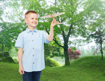 Smiling little boy holding a wooden airplane model Royalty Free Stock Photo