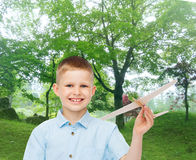 Smiling little boy holding a wooden airplane model Stock Photo