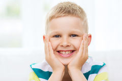 Smiling little boy at home. Childhood, happiness, home and people concept - portrait of smiling little boy at home royalty free stock photography