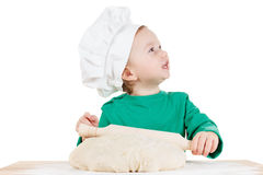Smiling little boy kneading dough for the cookies, isolated on white Royalty Free Stock Photo