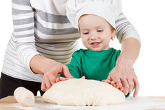 Smiling little boy kneading dough for the cookies, isolated on white. Smiling little cook and his mother kneading the dough for the cookies, isolated on white Stock Images