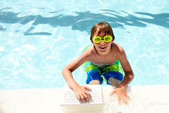 Smiling little boy with laptop in swimming pool Royalty Free Stock Photo
