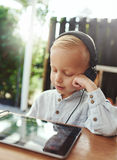 Smiling little boy listening quietly to his music Royalty Free Stock Images