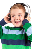 Smiling little boy listening to music in headphon Stock Images