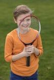 Smiling little boy looking through badminton racquet Stock Photos