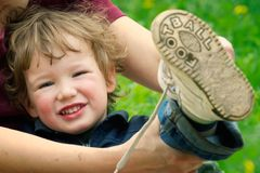 Smiling Little Boy with Loose Shoe. Mother putting football shoe on little boy, future soccer player Stock Image