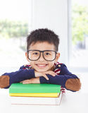 Smiling little boy lying on books Stock Photo