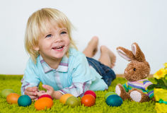 Smiling little boy lying with Easter eggs  on green carpet Stock Photos